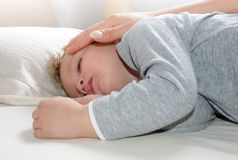 Little blond boy sleeping on his bed relaxed Stock Images