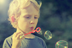 Little blond boy with soapy bubbles outdoors. Little blond boy is is blowing soapy bubbles outdoors. Photo is edited as a instagram effect Royalty Free Stock Photography