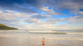 Little Blond Boy Stands in Foamy Waves of Shallow Sea on Beach stock video