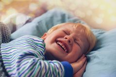 A little blond boy in striped pajamas with his hands under his cheek blinks, trying to sleep stock photo