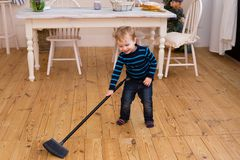Little blond boy sweeping the floor in the kitchen. Pretty boy 3 yers old helps parents with housework. Child cleaning room with broom. Child cleaning kitchen royalty free stock image