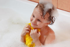Little blond boy with a washcloth bathes in the bathroom Royalty Free Stock Images