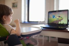 A little blond boy watching cartoons on the laptop while sitting on children`s chair.  stock image