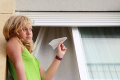 Little blond Caucasian girl with paper plane in window stock photos