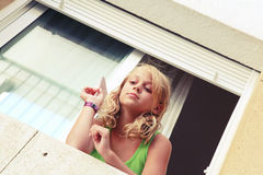 Little blond Caucasian girl with paper plane in the window Royalty Free Stock Image