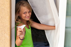 Little blond Caucasian girl with paper plane in window Stock Image