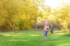 Little blond caucasian girl running in park or forest on bright autumn day. Child having fun playing outdoors. Happy healthy child. Hood activity and leisure Royalty Free Stock Images