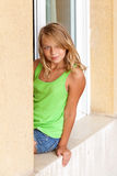 Little blond Caucasian girl in the window Royalty Free Stock Photo