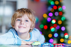 Little blond child playing with cars and toys at home royalty free stock image