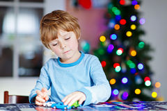 Little blond child playing with cars and toys at home stock image