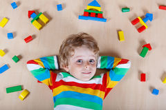 Little blond child playing with colorful wooden blocks indoor Royalty Free Stock Images
