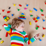 Little blond child playing with colorful wooden blocks indoor Royalty Free Stock Photos