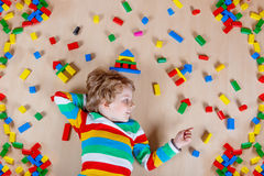 Little blond child playing with colorful wooden blocks indoor Stock Image