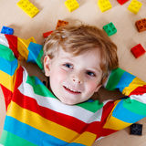 Little blond child playing with lots of colorful plastic blocks Stock Photography