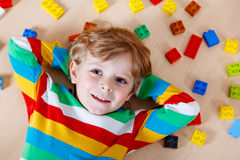 Little blond child playing with lots of colorful plastic blocks Stock Photo