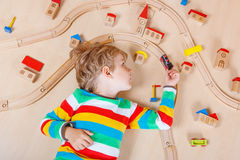 Little blond child playing with wooden railroad trains indoor Royalty Free Stock Photos