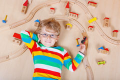 Little blond child playing with wooden railroad trains indoor Stock Photography