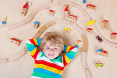 Little blond child playing with wooden railroad trains indoor Stock Photo