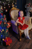Little blond child in a red dress Stock Images