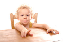 Little blond child sitting at table Stock Photography