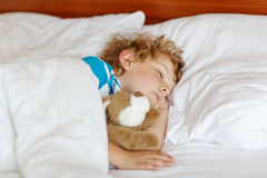 Little blond child sleeping in his bed with toy. Royalty Free Stock Photography