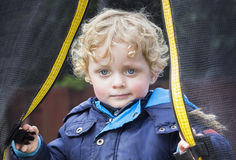 Little blond curly boy near a trampoline Royalty Free Stock Photography