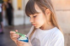 Little blond European girl eats ice cream Stock Images