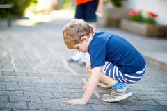 Little blond funny kid boy playing hopscotch on playground outdoors Stock Images