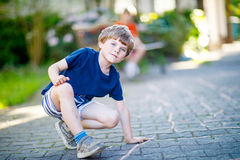 Little blond funny kid boy playing hopscotch on playground outdoors Stock Photography