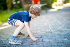 Little blond funny kid boy playing hopscotch on playground outdoors Stock Photo