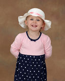 Little Blond Girl. A little blond girl with blue eyes and summer hat smiles widely in amusement stock image