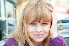 Little blond girl above light city background Royalty Free Stock Photography