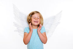 Little blond girl with angel- wings. Is smiling Royalty Free Stock Photos