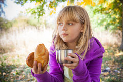 Little blond girl in autumn park eats small pies Stock Photos