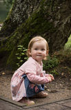 Little blond girl in beautiful dress kneeling on the ground Royalty Free Stock Photo