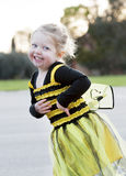 Little blond girl in bee costume dancing outdoors Royalty Free Stock Images