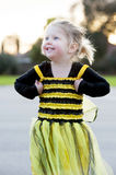 Little blond girl in bee costume dancing outdoors Royalty Free Stock Image