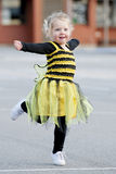 Little blond girl in bee costume dancing outdoors Royalty Free Stock Photography