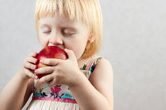 Little blond girl bites big red apple Stock Photos