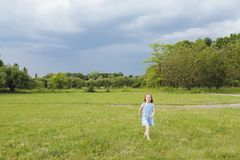 Little blond girl in a blue dress in the garden. Little girl laughing and having fun. Little blond girl in a blue dress in the garden.  Little girl laughing and Stock Photos