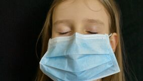 Little blond girl with blue eyes and long hair is posing on black backgound in surgical disposable mask for protection