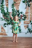 A little blond girl in a bright dress has lifted her arms up in a room decorated with flowers. Little girl in a bright dress in a room decorated with flowers Stock Image