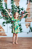 A little blond girl in a bright dress has lifted her arms up in a room decorated with flowers. Little girl in a bright dress in a room decorated with flowers Stock Images