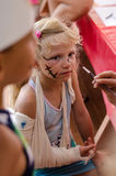 Little blond girl with broken hand and face painting Stock Images