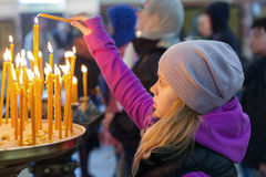 Little blond girl with candles in Orthodox Church Stock Photo