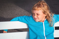 Little blond girl in casual sport outwear relaxes Stock Photography