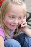 Little blond girl on a cellphone. Little girl talking on the cell phone, with long blond hair, shallow depth of field Royalty Free Stock Photo
