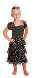Little blond girl in dark dress with polka dots . Cute little blond girl in a dark dress with polka dots, bows and sunglasses on her head on white background royalty free stock photos
