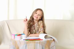 Little blond girl drawing at home on sofa. And looking above Royalty Free Stock Image