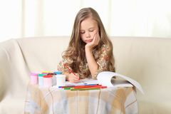 Little blond girl drawing at home on sofa. Little blond girl drawing  at home on sofa Royalty Free Stock Images